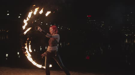 espectador : Attractive firegirl performing amazing skill of spinning burning fans creating fascinating sight of fiery figures at dusk. Pink-haired woman fireshow artist transfering to viewer magic energy of fire.