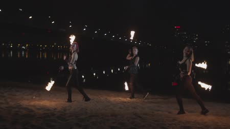 пожар : Skillful trio of poisters spinning fire poi dancing on sand hypnotizing with motion of flame at dusk of night city. Young firegirls and man performing mastery of poing during dance on riverbank. Стоковые видеозаписи