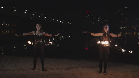ustalık : Stylish firegirls performing amazing synchronous work with fire hoops during night fireshow on river bank. Women fireshow performers twisting hula hoops with burning wicks at waist standing by river.