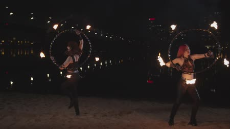 ustalık : Charming firegirls performing mastery of work with fire hoops standing on riverside at dusk of city. Young females performers twisting hula hoops with lit torch wicks by hands creating fiery circles.
