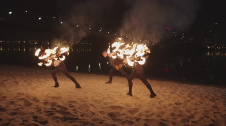 water show : Young fireshow artists performing amazing trick of rolling burning dragon staves at dusk. Man and firegirls standing on sand by river with fire staves rolling over body during fantastic fireshow. Stock Footage