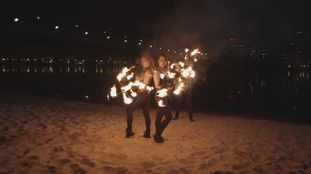 fireshow : Fascinating sight of energy, motion and power of living fire created by skillful fireshow artists standing on sand by river at night. Stylish firegirls and man rolling flaming dragon staves at dusk.