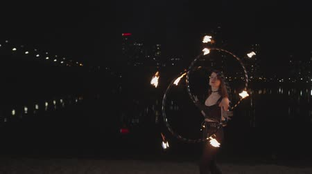 ustalık : Redhead female fireshow performer spinning two hula hoops with burning wicks by hands stepping back and forth during fireshow on riverside. Lovely firegirl performing skill of twisting hoops at dusk.