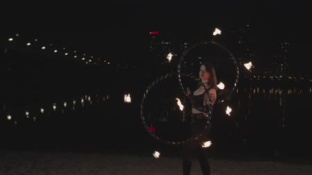 ustalık : Attractive female fireshow artist performing mastery of work with two fire hula hoops holding hands and stepping smoothly on sand. Stylish firegirl spinning hoops during night fireshow by river.
