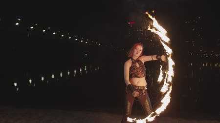éjszakai élet : Skillful female artist performing art of spinning fans during amazing fireshow performance near river at night. Lovely firegirl creating wonderful fiery figures hypnotizing with motion of flame. Stock mozgókép