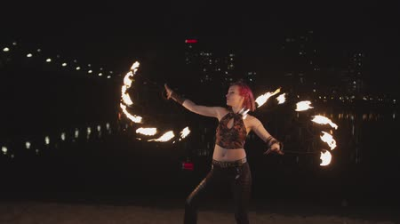 water show : Pretty pink-haired firegirl creating fantastic fiery figures spinning burning fans mesmerizing with energy of fire at dusk. Young woman fireshow artist performing skill of spinning fans on riverside. Stock Footage