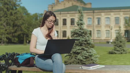 remotely : Close-up of tired student networking online on laptop preparing for classes sitting on park bench in the morning. Fatigue woman falling asleep studying online outdoors in front of university building. Stock Footage