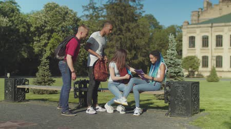 одноклассник : Young distressed african american female student crying looking at exam results in front of university. Caring multinational friends comforting sad classmate sitting on park bench in university campus