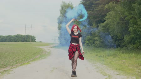 regozijo : Happy stylish female hipster with colored smolke bomb rejoicing life and enjoying freedom while walking on countryside road. Young pink-haired woman walking on dusty track in veil of colorful smoke.