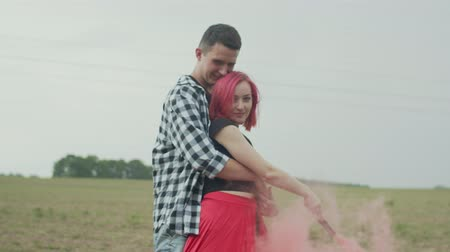 mansão : Stylish pink-haired woman holding smoke bomb and mans hand during walk in countryside. Couple of hipsters cuddling outdoors, male hugging lovely female by waist, wind blowing color smoke over field.