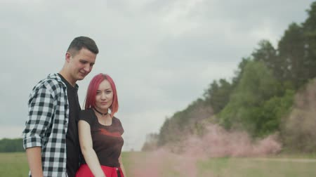 loved : Close-up of stylish young people spending leisure in countryside, charming pink-haired woman with red smoke bomb and loved man bonding in nature. Summer wind blowing colorful smoke from bomb outdoors
