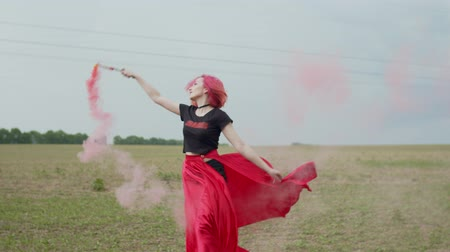 gonna : Close-up of stylish female in long bright red skirt holding color smoke bomb circling during walk across country field. Elegant woman enjoying freedom and nature on windy day in countryside.. Filmati Stock