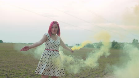 sedutor : Close-up of attractive female in short polka-dot dress walking with color smoke bomb in hand outdoors against natural landscape background. Seductive woman creating veil of colored smoke in nature. Stock Footage