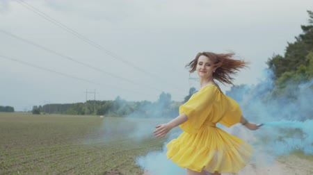 whirling : Portrait of pretty female in bright summer dress walking across country field with smoke bomb in hand. Joyful woman creating veil of color fume and whirling over countryside landscape background.