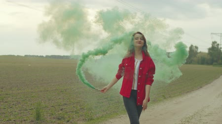 závoj : Attractive female holding color smoke bomb enjoying freedom of countryside leisure during walk on country road. Young redhead woman in bright jacket whirling creating veil of colorful smoke around.