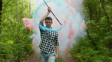 going round : Portrait of short cut male walking through circle of colored smoke generated by spinning staff in forest path. Young man skillfully juggling staff with smoke bombs going along summer greenwood. Stock Footage