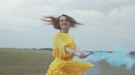whirling : Close-up of lovely woman in short yellow dress circling in the middle of country field with color smoke bomb in hand. Attractive female creating veil of colorful fume carried away by wind over field.