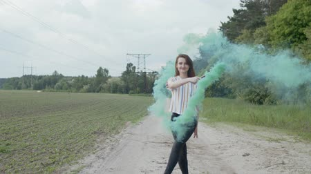 veli : Attractive redhead woman circling in clouds of colorful smoke blowing away by wind. Smiling stylish dressed female walking on rural road with colored smoke bomb enjoying summer vacation in countryside