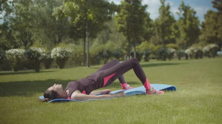 sakk : Chinese fitness woman training glutes lying on fitness mat during workout on green park lawn. Young asian athletic female doing sport exercises on sunny day working on gluteal muscles in city park.