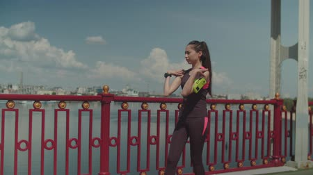 um : Asian athletic woman with armband stretching muscles of body after morning cardio training on river footbridge. Chinese female jogger in sportswear doing warm up at the end of fitness workout outdoor.