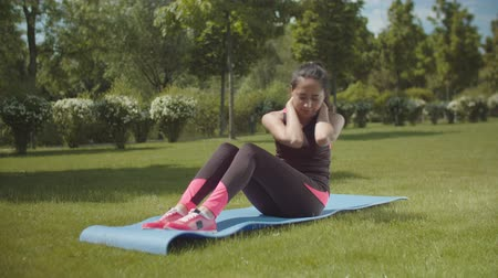 construção muscular : Sporty asian woman lifting body from prone position working on lateral abdominal muscles while lying on fitness mat. Chinese female athlete doing sport exercise on abs during workout on park lawn. Vídeos