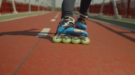 inline : Womans feet in roller skates slowing down at speed showing skill of soul wheel slide. Active skillful female braking, making power slide while rollerblading along footpath, urban street hobby concept