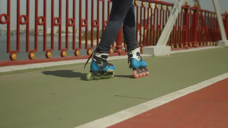inline skating : Close-up of young female feet in roller skates rollerblading forwards crossover and crisscross on river bridge. Woman roller enjoying outdoor riding along city footpath, street sport activity concept. Stock Footage