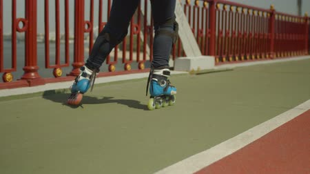 inline skating : Close-up of womans feet in roller skates and knee pads skating in cross position on city river footbridge. Active skillful female roller enjoying outdoors hobby rollerblading on sunny summer day. Stock Footage