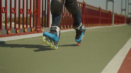inline : Close-up of active female feet in roller skates and knee pads riding backwards crossover, crisscross and cross along river bridge path. Young skillful woman enjoying rollerblading outdoors in city.