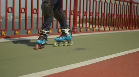 inline : Close-up of female roller legs in roller skates and knee pads skillfully skating backwards crossover and slide along city bridge footpath. Young woman rollerskating enjoying active outdoors hobby.