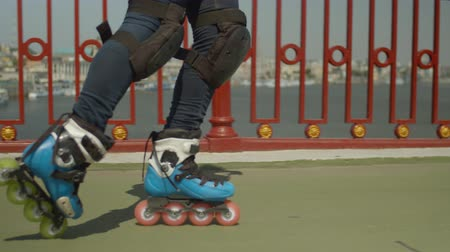inline skating : Close-up of skillful womans legs in roller skates and knee pads doing cross position riding backwards and forwards crisscross along city river bridge footpath. Active woman rollerskating outdoors. Stock Footage
