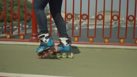 inline skating : Close-up of young womans legs in roller skates showing skill of rollerblading backwards crossover during freeride in the city. Skillful active female rollerskating along city bridge footpath. Stock Footage