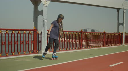 inline skating : Active female in helmet, knee pads and handhelds rollerblading forwards, backwards and crisscross along river bridge path. Positive skillful woman with afro-braids enjoying rollerskating on footbridge.