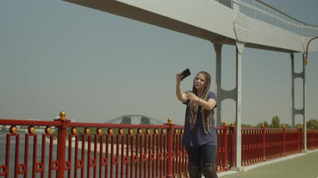 inline : Happy woman with afro-braids posing for selfie photo and chatting on phone while riding roller skates on river bridge. Joyful female roller taking selfie shot on smartphone and talking during ride. Stock Footage