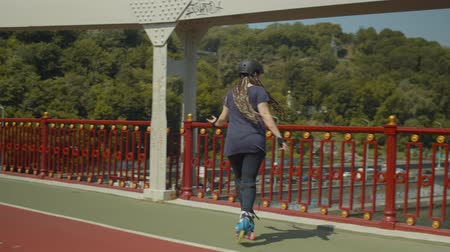 inline : Positive joyful woman with afro-braids skillfully riding roller skates along bridge footpath. Active female in protective outfit enjoying rollerblading forwards, backwards and crisscross on city bridge. Stock Footage