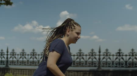 ветреный : Portrait of happy female with long ponytail from afro-braids enjoying freedom and speed rollerskating on windy sunny day. Positive woman roller riding in summer park while wind waving her hair.
