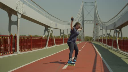 regozijo : Happy woman in roller blades slowing down at speed showing good skill of soul wheel slide. Active positive female rejoicing while braking rollerskating along river bridge footpath on windy sunny day. Stock Footage