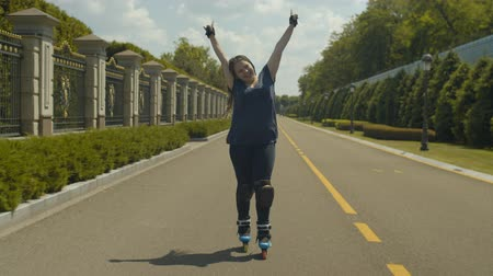 inline : Happy woman roller in roller blades, knee pads and handhelds enjoying freedom and speed riding on public park. Positive female with long afro-braids having fun rollerblading anfd gesturing outdoors.