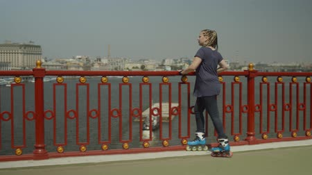 inline : Positive female in inline roller skates taking break to enjoy picturesque view from city river bridge. Young woman roller with afro-braids leaning on footbridge railing looking at scenic cityscape. Stock Footage