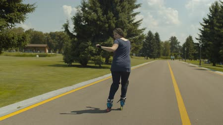 inline skating : Stylish woman with beautiful long hair braided in many pigtails showing skill of backward sliding on roller blades along public park alley. Carefree female roller enjoying active leisure outdoors.