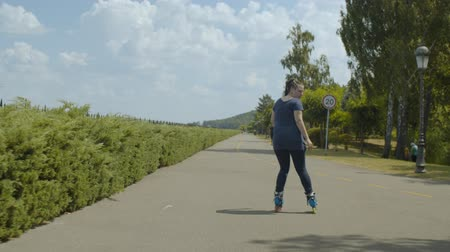 inline : Young skillful woman rollerblading backwards along path of well-kept public park. Female skater showing skill of backward riding roller blades, active hobby, positive healthy sport lifestyle concept.
