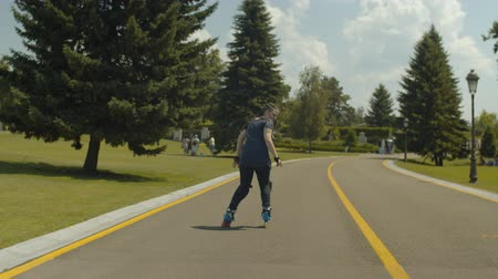 колено : Young carefree joyfiul female showing skill of backward rollerblading at good speed on public park footpath. Active woman in protective equipment rollerskating over nature landscape background.