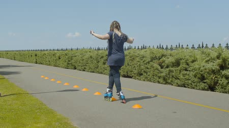 inline : Rear view of skillful woman rollerblading inline roller skates past cones on park footpath. Active female with ponytail from afro-braids training skill of crisscross ride during inline slalom outdoor. Stock Footage