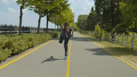 inline skating : Playful female rollerblading along green park alley comically imitating superman riding one roller skate and stretching arm forward. Young woman with ponytail from afro-braids having fun during ride. Stock Footage
