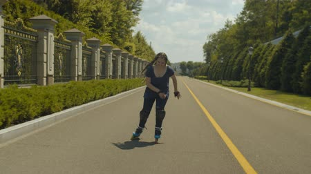 inline skating : Joyful woman roller with long afro-braids riding inline roller skates at speed along park alley. Positive female in roller blades, knee pads and handhelds rollerskating among greenery of public park. Stock Footage