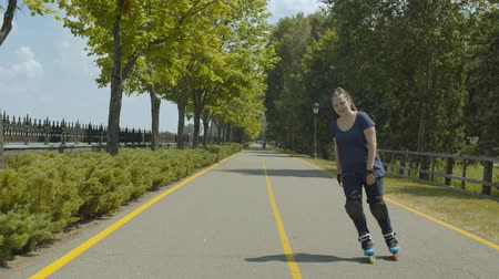 inline : Joyful woman in protective equipment rollerblading along well-kept summer park alley. Positive female roller with ponytail from afro-braids riding among green trees enjoying outdoor summer leisure.