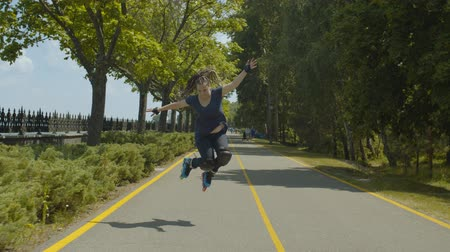 inline skating : Smiling female skater with long afro-braids making jump stunt during speed skating on roller blades. Cheerful woman in protective outfit rollerblading along public park footpath during sport training.