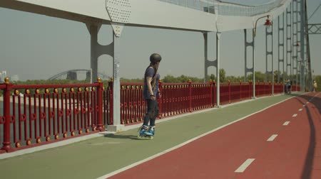 inline : Young woman in protective outfit riding roller blades forwards and after turning backwards crossover on city bridge. Active female making turn while rollerblading along river bridge footpath. Stock Footage
