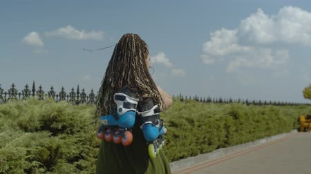 inline skating : Portrait of happy woman walking along park footpath with roller blades hanging on shoulder. Smiling female roller turning around and winking during walk after rollerblading in summer park. Stock Footage