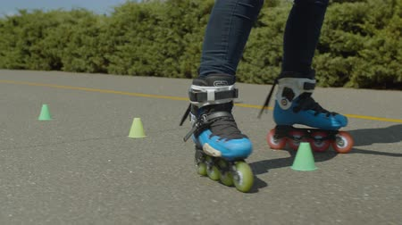 inline : Close-up of female legs in roller blades riding forward crisscross through cones during workout in public park. Woman inline skating stunt of crisscross ride round cones standing in line on alley.